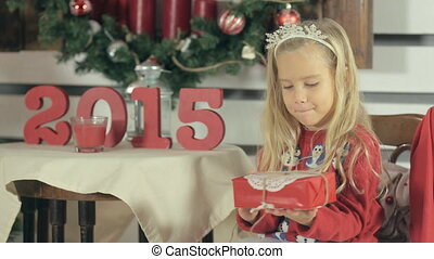 Little blond girl with long hair and wearing a red sweater with snowmens shakes Christmas gift