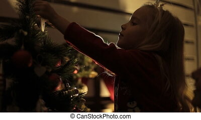 Little blond girl with long hair decorates Christmas tree with her mother in the dark