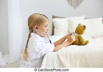 Little blond girl with stethoscope playing with teddy bear