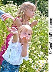 little blond girls in daisy field