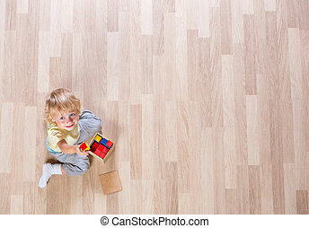 Little blond kid boy playing with colorful building blocks on floor top view