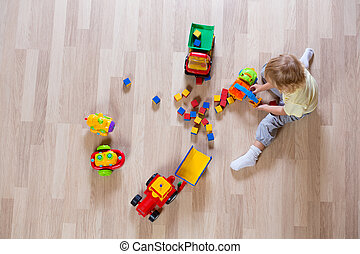 Little blond kid boy playing with colorful car toys on floor top view