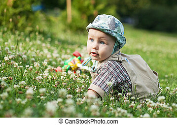 little blond kid playing on a summer meadow