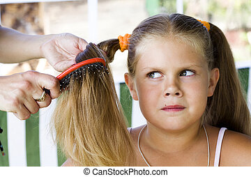 Little blond long hair girl has haircare by stylist.