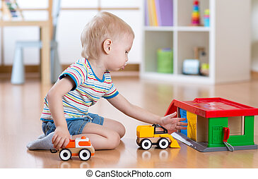 Little blond toddler kid boy plays with toy car