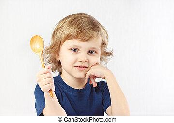 Little blonde boy holding a wooden spoon
