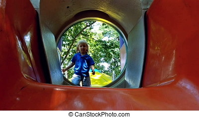 Little blonde boy playing on slide in the park