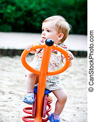 Little blonde boy playing on the swing. Summer