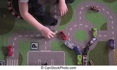 Little blonde boy plays with cars on carpet