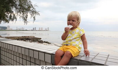 little blonde child eats biscuits at seafront