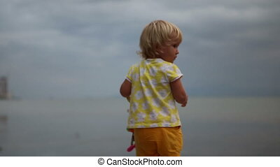 little blonde child holds toy and soap bubbles fly around her against sea and clouds at city seafront