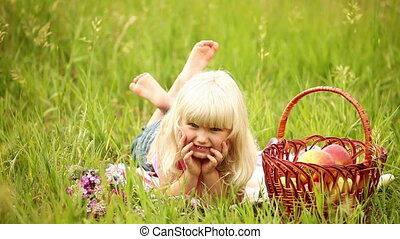 Little blonde child lying on the gr