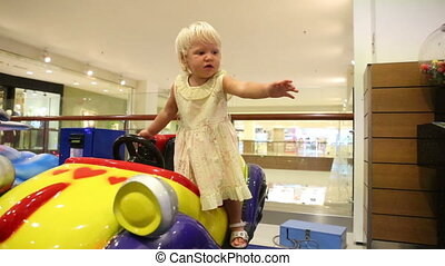 little blonde child play in toy car