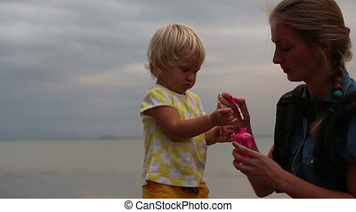 little blonde child play with mother blowing soap bubbles