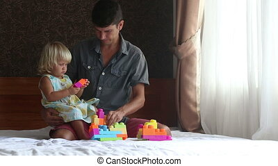 little blonde daughter plays toy constructor with father