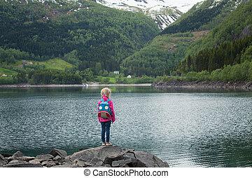 little blonde girl at the shore of norwegian lake