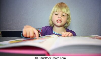 Little blonde girl considers pictures in the book