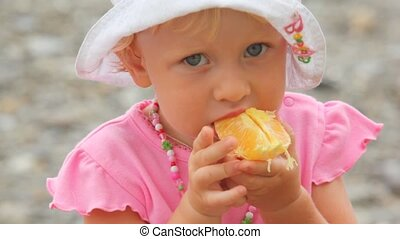 little blonde girl dressed in panama eats orange outdoor