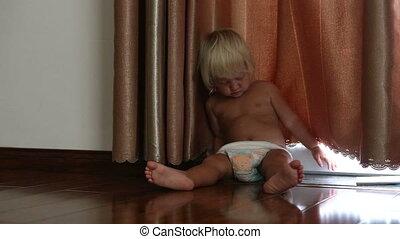 little blonde girl falls asleep on floor near curtain