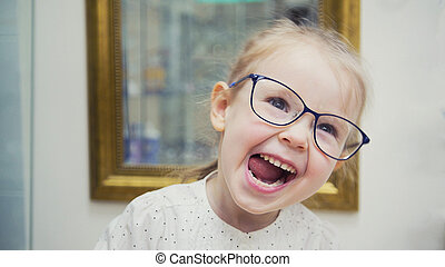 Little blonde girl in hall of ophthalmology clinic have fun and plays with glasses