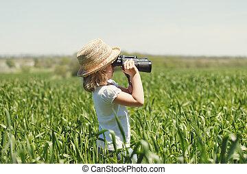 Little blonde girl in looking through binoculars outdoor