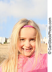 little blonde girl on beach smiling with gapis in teeth