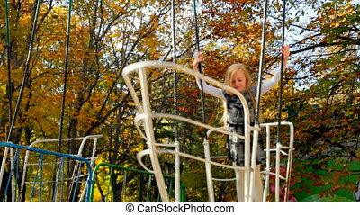 Little blonde girl on swing boat