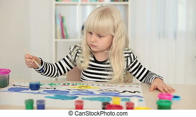 Little blonde girl paints pictures