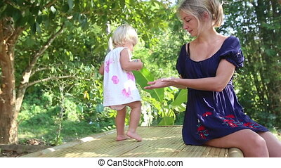 little blonde girl play with  her mother