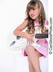 little blonde girl playing electrical guitar
