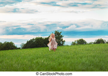 Little blonde girl running on a green meadow