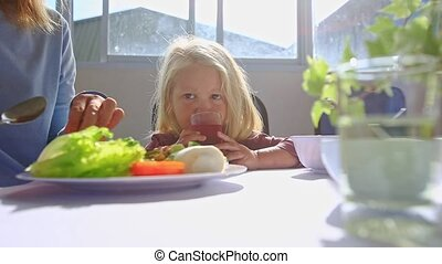Little Blonde Girl Sits at Table Drinks Juice Near Mother Eating Breakfast