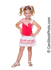 Little blonde girl stands against the white