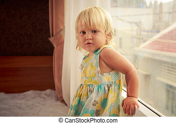 little blonde girl stands by window side-view