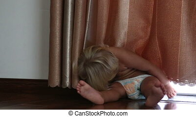 little blonde girl wakes up after sleeping on floor by curtain