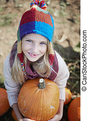 Little blonde girl with big pumpkin