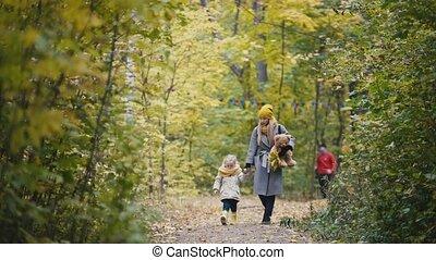 Little blonde girl with her mommy walks in autumn park alley, sportsmen runs at background