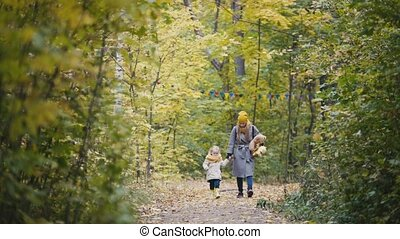Little blonde girl with her mommy walks in autumn park alley