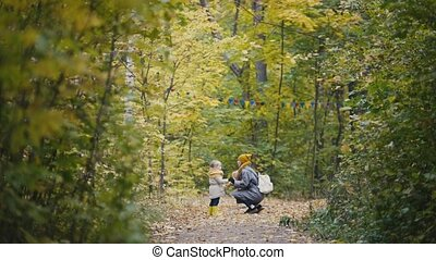 Little blonde girl with her mommy whispering in autumn park alley