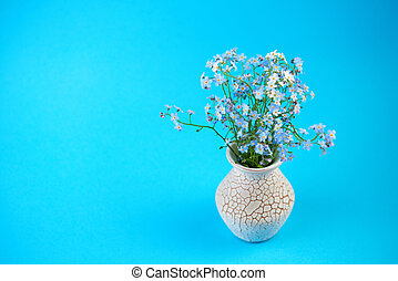 Little blue flowers in vase on colored background