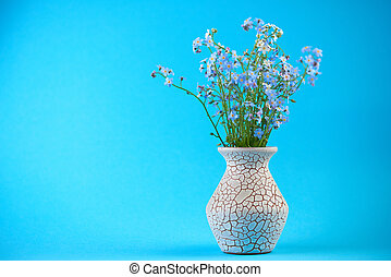 Little blue flowers in vase on colored background with empty space for you text