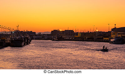 Little boat for fishing in Fiumicino port at sunrise.