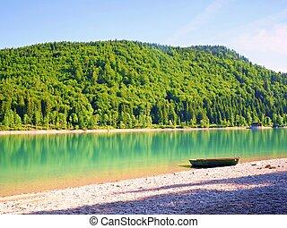 Little boat on lake shore, beautiful summer nature.
