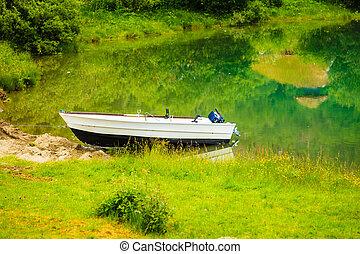 Little boat on water shore