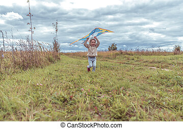 Little boy 3-5 years old, happy smile launches a kite in park, feel happy. Casual warm clothes with hood. Autumn day. Free space for copying text. Emotions of happiness and pleasure.