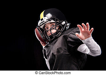 Little boy american football player in uniform throwing ball