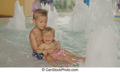 Little boy and baby girl having fun in the pool. Brother and his sister having fun in the pool