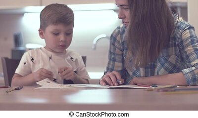 Little Boy And Beautiful Mother Draw Together