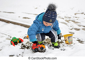 A little boy came with toys to meet the first snow