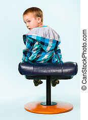 Little boy on posing with a footstool, studio shot and light blue background